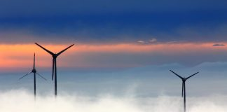 Wind turbines above low clouds